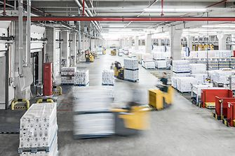 Forklifts carrying packages in production